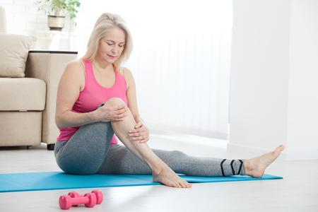 Mujer de mediana edad que sufre de dolor en la pierna en casa, primer plano. Concepto de lesión física. Enfoque selectivo.