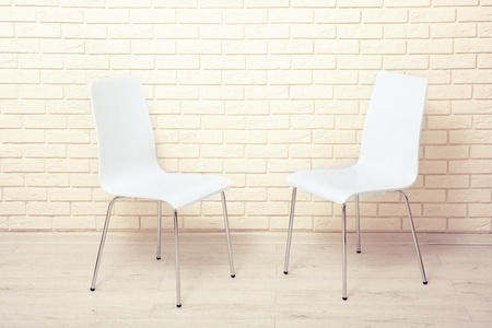 White chairs near the white wall for interior or graphic backgrounds. The chairs can be used to represent interview sessions or waiting rooms for ads purpose. Stock fotó
