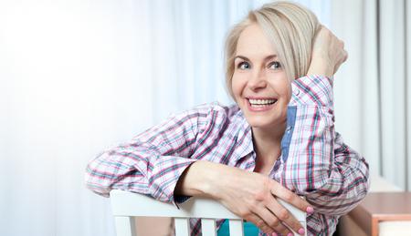 Atrakcyjna kobieta w średnim wieku, patrząc w kamerę, relaks w domu. Piękna twarz z bliska.