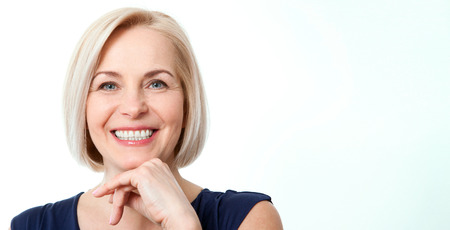 Attractive middle aged woman with beautiful smile on white background