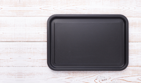 Empty baking tray for pizza close up on wooden background top view horizontally. Mock up for design