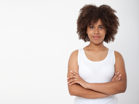 Portrait of beautiful black woman isolated. Atractive brunette dark-skinned woman in a white tank top. 写真素材