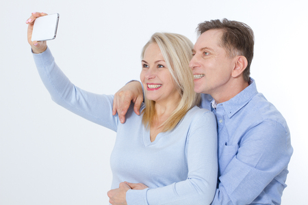 happy couple taking selfie with smartphone isolated on white