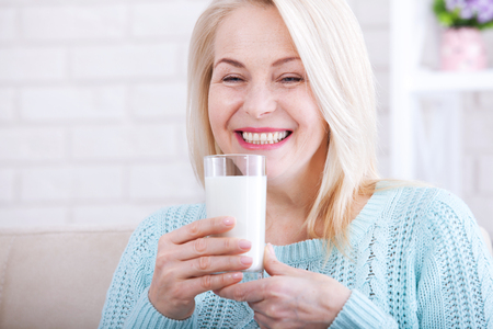Happy middle aged woman drinking milk. Face close up. Stock Photo
