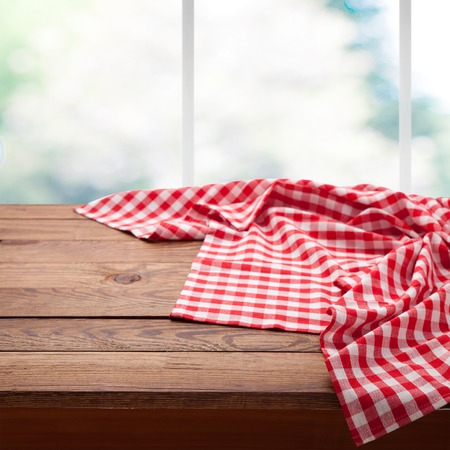 Red checkered tablecloth on wooden table on empty wooden table near the window in kitchen. 写真素材