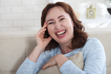 Happy female face. Attractive and beautiful middle aged woman sitting on sofa .
