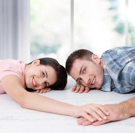 Happy young couple, lying on the floor, look at each other and dream of furniture for a new apartment. Mock up