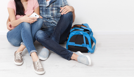 A woman and a man are sitting in a new apartment using a smartphone. A young couple chooses a wedding trip.