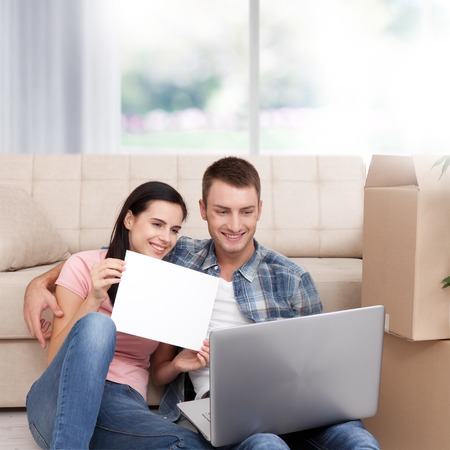Beautiful young couple using laptop communicates via Skype. The woman smiles and shows a blank sheet of paper.