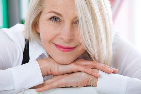 Belle femme blonde d'âge moyen avec un sourire radieux assis au bureau en regardant la caméra
