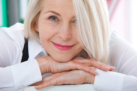 Lovely middle-aged blond woman with a beaming smile sitting at office looking at the camera Stock Photo