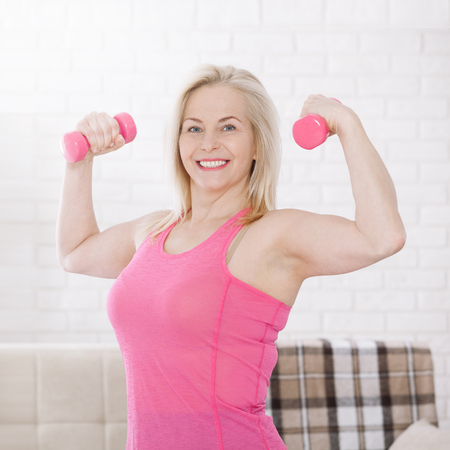 Happy middle aged woman lifting dumbbells at home in the living room