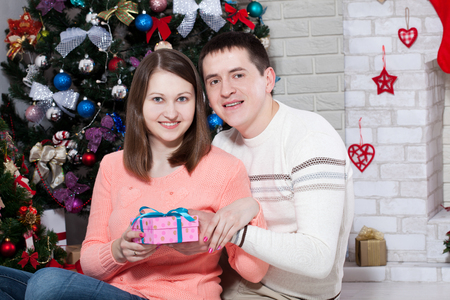 Cheerful couple with gift in hands enjoying together on Christma Stock Photo