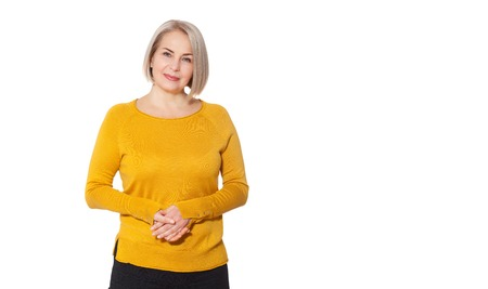 Middle aged blonde emotionally posing in a studio. Happy woman in yellow bright sweater on white Banque d'images