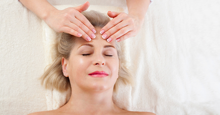 Attractive woman with close eyes taking skin care. Massage face selective focus. Standard-Bild - 122842896