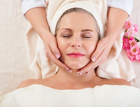 Portrait of beautiful woman in spa environment. middle aged woman doing facial massage in a spa salon Standard-Bild - 122842821