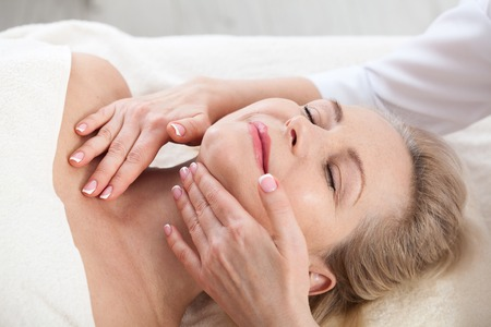 Face massage in spa macro. Attractive woman with close eyes taking skin care.