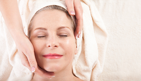 Face massage in spa macro. Attractive woman with close eyes taking skin care. Standard-Bild - 122842829