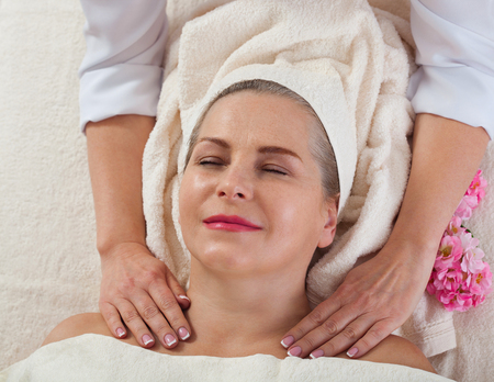 Face massage in spa macro. Attractive woman with close eyes taking skin care. Standard-Bild - 122842834