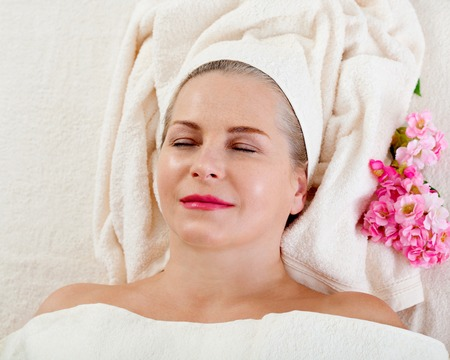Face massage in spa macro. Attractive woman with close eyes taking skin care. Standard-Bild - 122842836