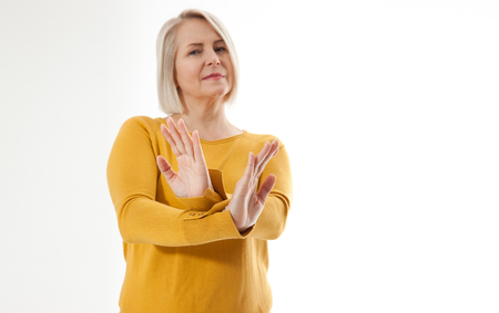 Excited middle aged woman showing the sign of stop, neglect negation and reluctance Standard-Bild - 125306004