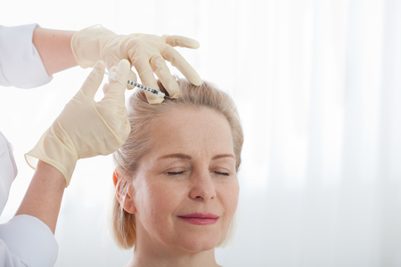 Middle aged woman gets cosmetic injection in her forehead. Standard-Bild - 125306050