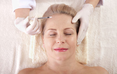 Middle aged woman gets cosmetic injection in her forehead. Standard-Bild - 125306012