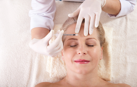 Middle aged woman gets cosmetic injection in her forehead. Standard-Bild - 125306027