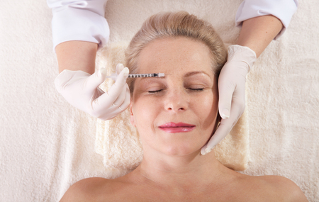 Middle aged woman gets cosmetic injection in her forehead. Standard-Bild - 125306028