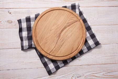 Pizza board, with tablecloth on wooden table and summer Standard-Bild - 129144349