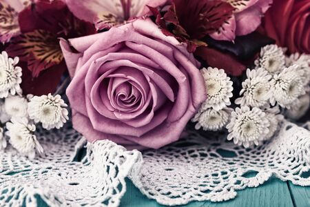 Bouquet of pink and white roses on a blue wooden table with a white tablecloth with lace Standard-Bild - 129144120