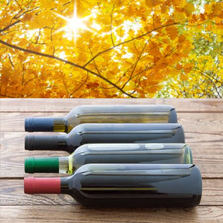 Red wine bottles stacked on wooden table. Standard-Bild - 129144130