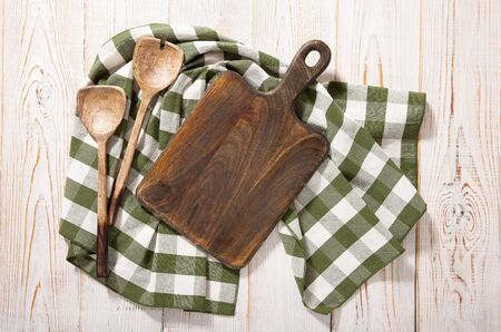 Cutting board and napkin on white wooden table. Standard-Bild - 129144126