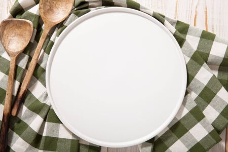Black plate or tray, or pizza board, with tablecloth on wooden table. Top view mockup Standard-Bild - 129144152