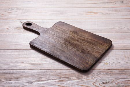 Cutting board on the wooden background. Top view. Standard-Bild - 129144153