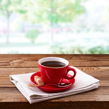 Red cup of tasty coffee on napkin, on wooden table. Standard-Bild - 129143849