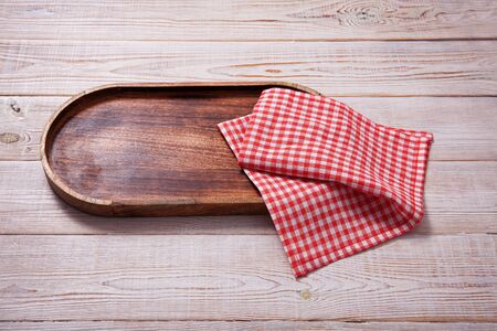 Wooden tray and napkin on white wooden table. Standard-Bild - 129143847