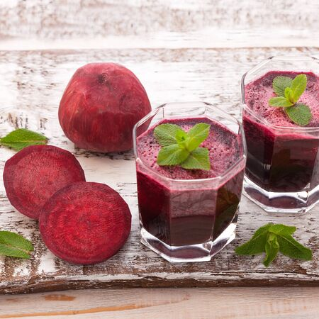 Healthy and healthy detox smoothies or juice from raw beets and spinach in glass bottles on wooden Standard-Bild - 129143846
