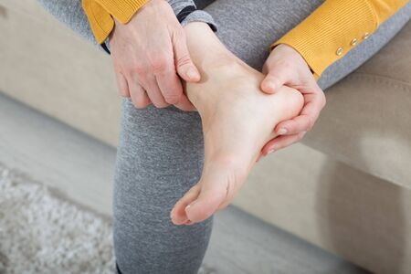 Ankle pain, painful point. Unhappy woman suffering from pain in leg at home. Physical injury concept. Stockfoto - 132021423