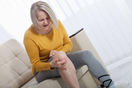 Knöchelschmerzen, schmerzhafter Punkt. Unglückliche Frau, die zu Hause unter Schmerzen im Bein leidet