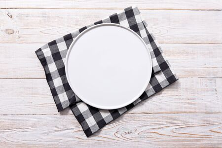 Black plate or tray, or pizza board, with tablecloth on wooden table. Top view mockup Stock Photo