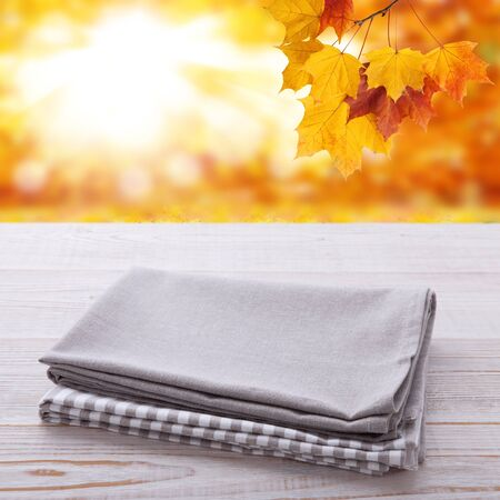 Empty wooden deck table with tablecloth over bokeh autumn leaves background Stockfoto