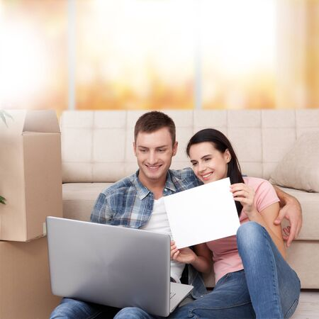 Beautiful young couple using laptop communicates in video chat. A woman is smiling and showing blank piece of paper. Фото со стока