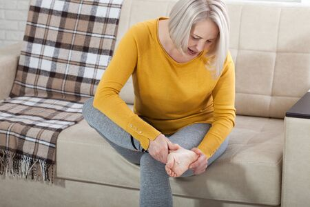 Ankle pain, painful point. Unhappy woman suffering from pain in leg at home Stock Photo - 140193806