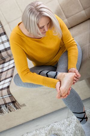 Middle-aged woman suffering from pain in leg at home, closeup. Physical injury concept. Stock Photo