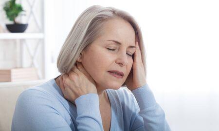 Frau, die unter Stress oder Kopfschmerzen leidet, die vor Schmerzen das Gesicht verzieht, während sie den Nacken mit der anderen Hand an ihre Schläfe hält, mit Exemplar. Konzeptfoto mit Angabe der Schmerzstelle.