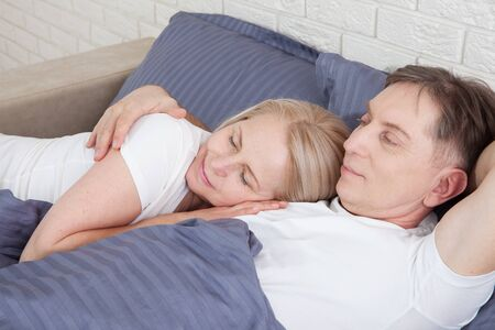 Happy couple is lying in bed together. Enjoying the company of each other. Archivio Fotografico