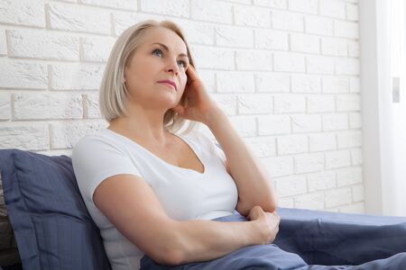 Pensive woman sitting on the bed at home Standard-Bild