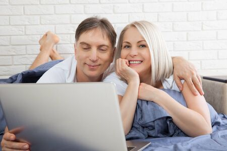 Beautiful amorous couple using laptop, on bed. Beautiful woman and handsome man read the news on internet. Concept relationship.