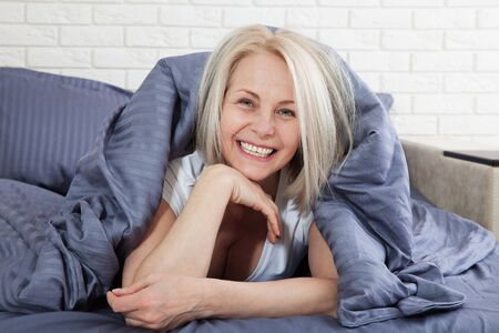 Smiling woman under a duvet in her bedroom Zdjęcie Seryjne